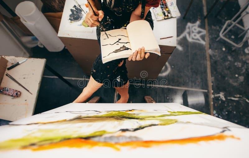Pintor de sexo femenino que se sienta en el estudio que hace un dibujo imagenes de archivo