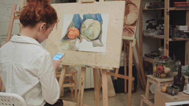 Pintor de sexo femenino que usa smartphone en taller foto de archivo libre de regalías