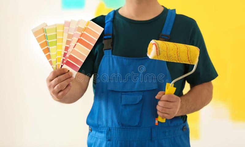 Pintor de sexo masculino en uniforme con las muestras de la paleta de colores y cepillo del rodillo en fondo colorido imagen de archivo