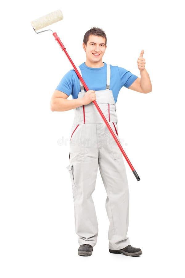 Pintor de sexo masculino que sostiene un rodillo y que da un pulgar para arriba imagenes de archivo