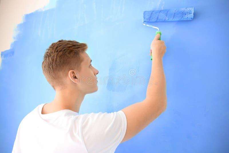 Pintor de sexo masculino que usa el rodillo para restaurar el color de la pared dentro imagen de archivo libre de regalías