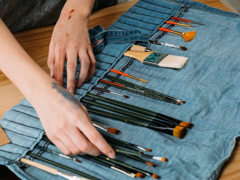 Pintor del equipo del artista profesional que elige el cepillo imagen de archivo