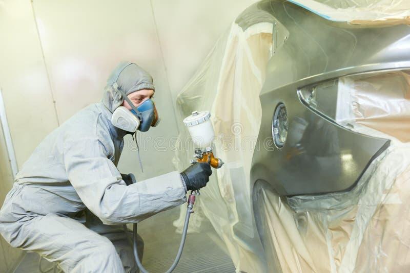 Pintor do reparador na capota do carro do automóvel da pintura da câmara foto de stock royalty free