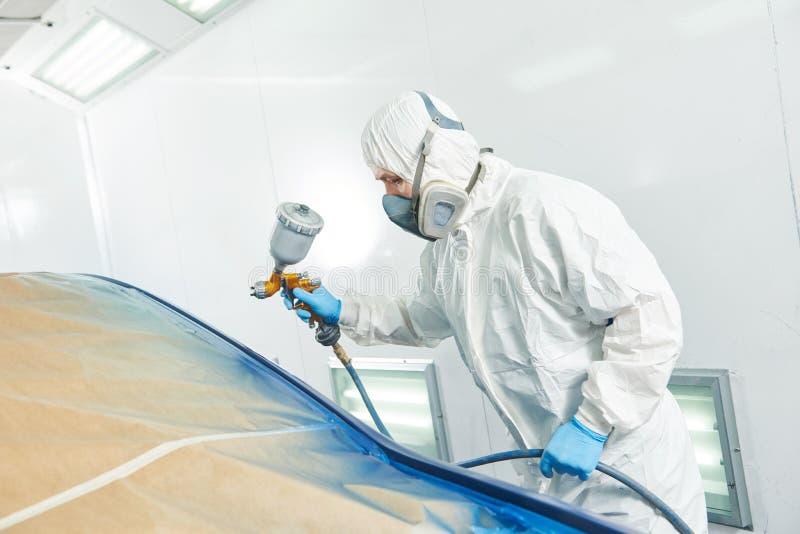 Pintor do reparador no amortecedor do carro do automóvel da pintura da câmara imagens de stock