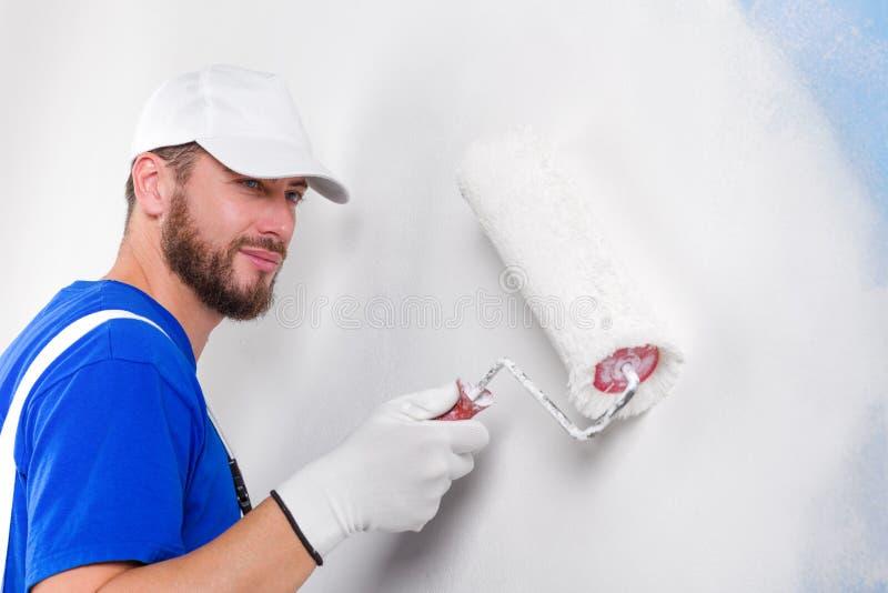 Pintor en los overoles blancos, camiseta azul imagen de archivo
