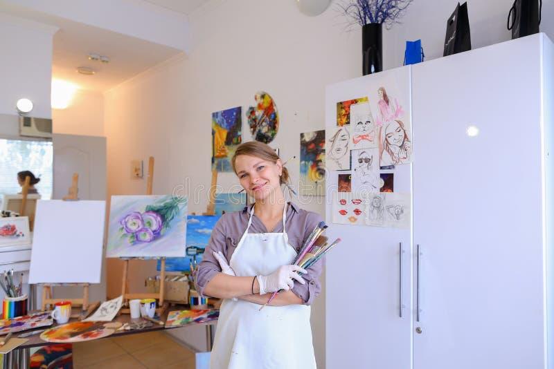 Pintor hermoso de las mujeres que presenta y que sonríe, riendo en cámara imágenes de archivo libres de regalías