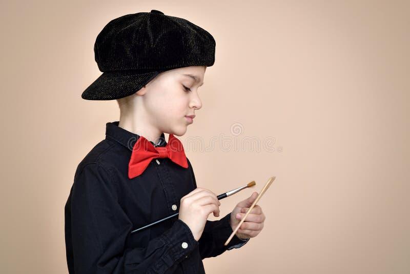 Pintor joven con la corbata de lazo roja y camisa y casquillo negros que sostienen la brocha y la paleta del arte fotografía de archivo libre de regalías