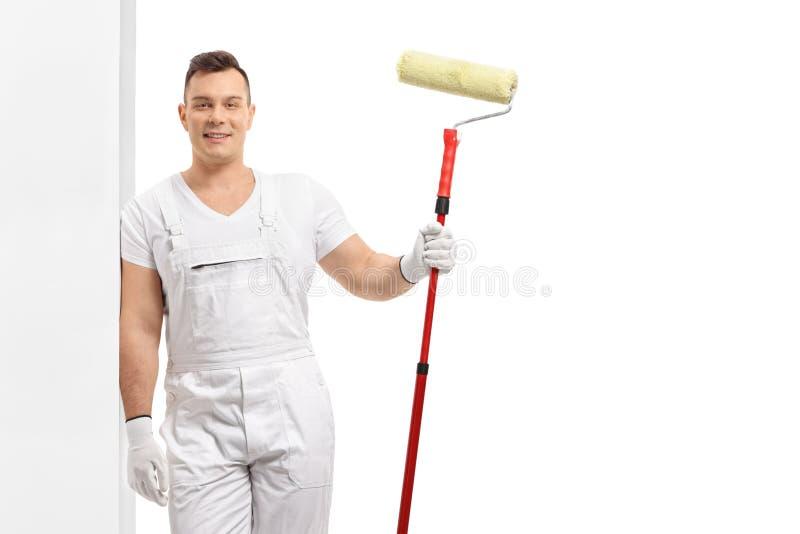 Pintor joven con un rodillo de pintura que se inclina contra una pared fotos de archivo