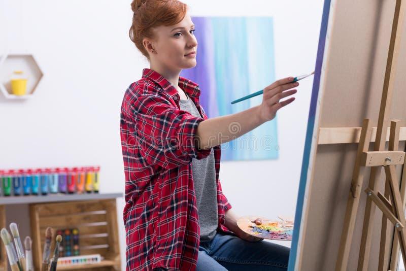 Pintor joven en el trabajo en su estudio fotografía de archivo libre de regalías