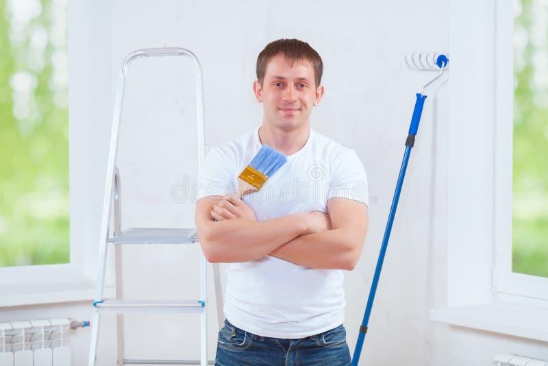 Pintor joven hermoso con la brocha cruzada del azul de la tenencia de brazos fotos de archivo