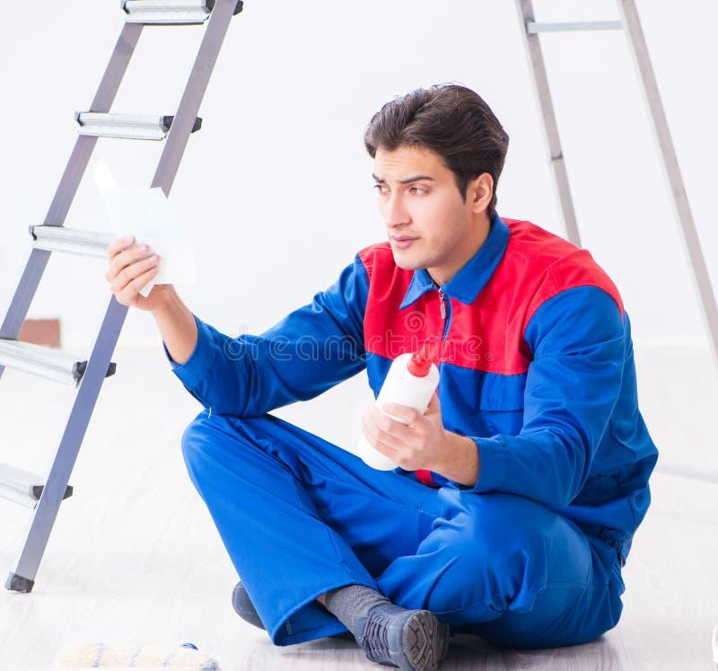 Pintor joven que intenta hacer juego los colores para el trabajo de pintura imagen de archivo