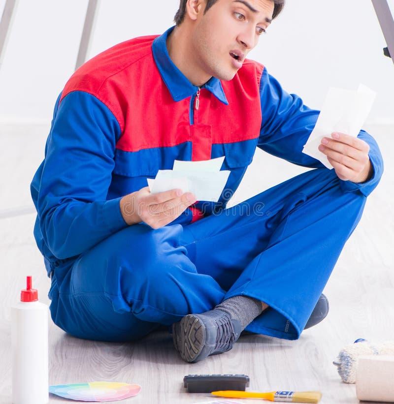 Pintor joven que intenta hacer juego los colores para el trabajo de pintura fotografía de archivo