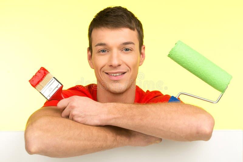 Pintor joven que se sienta sosteniendo las herramientas de la pintura fotos de archivo
