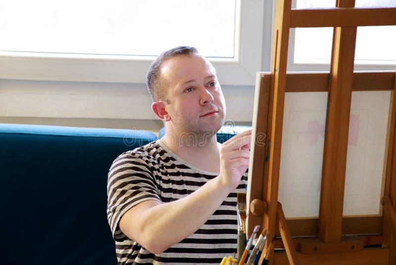 Pintor masculino do artista que trabalha na oficina com lona na armação de madeira da mesa de projeto no estúdio da pintura da ar ilustração do vetor