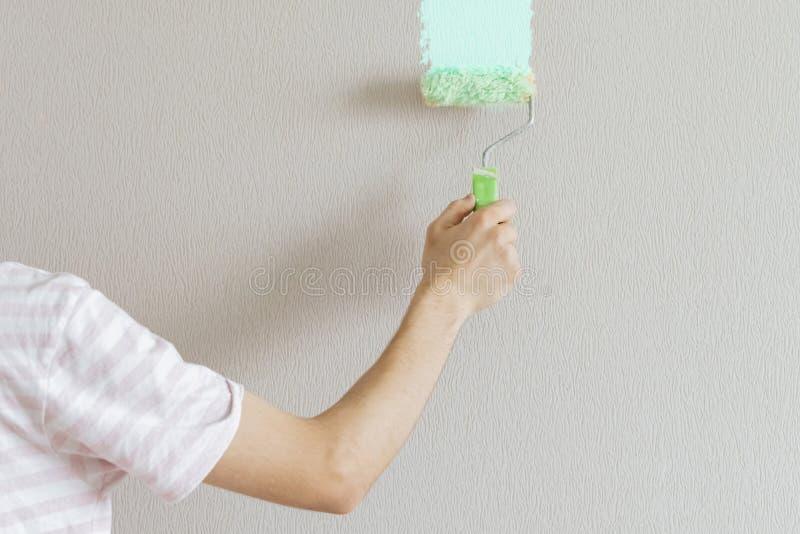 Pintor masculino isolado que trabalha e para pintar a parede textured, curso f da escova foto de stock