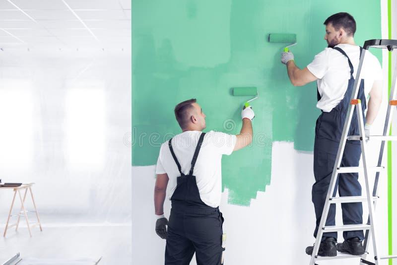 Pintor na escada que pinta um verde da parede ao redecorar inter fotos de stock