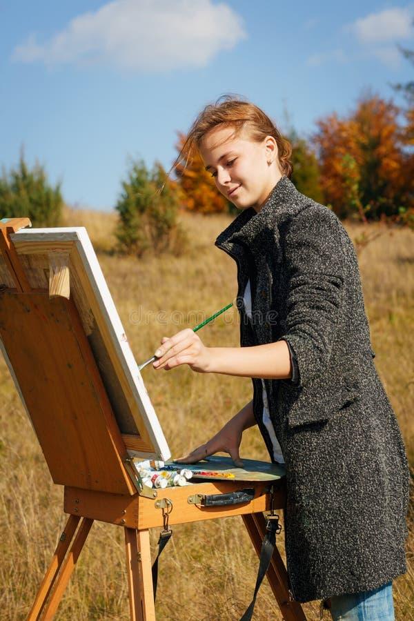 Pintor novo no trabalho nas montanhas imagem de stock royalty free