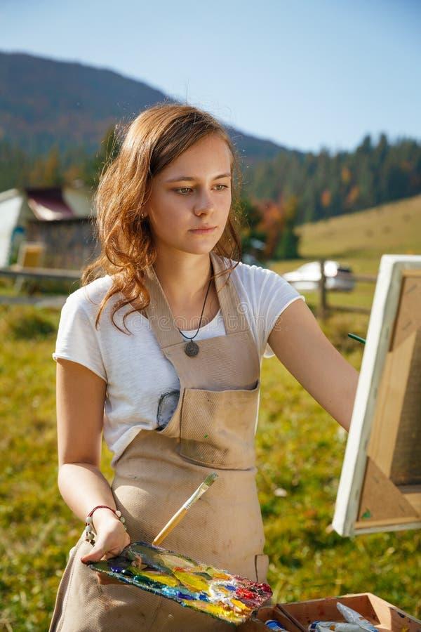 Pintor novo no trabalho nas montanhas foto de stock royalty free