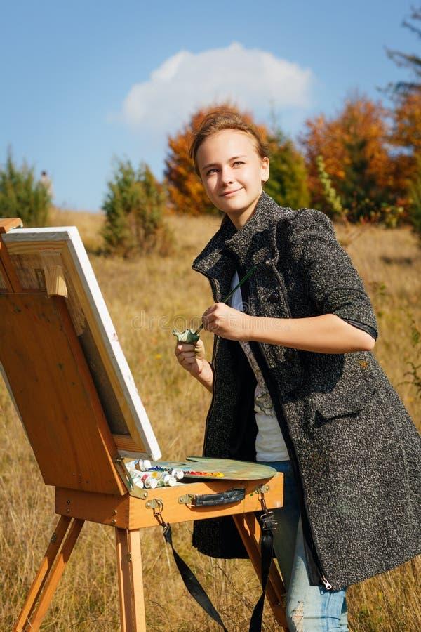 Pintor novo no trabalho nas montanhas fotografia de stock