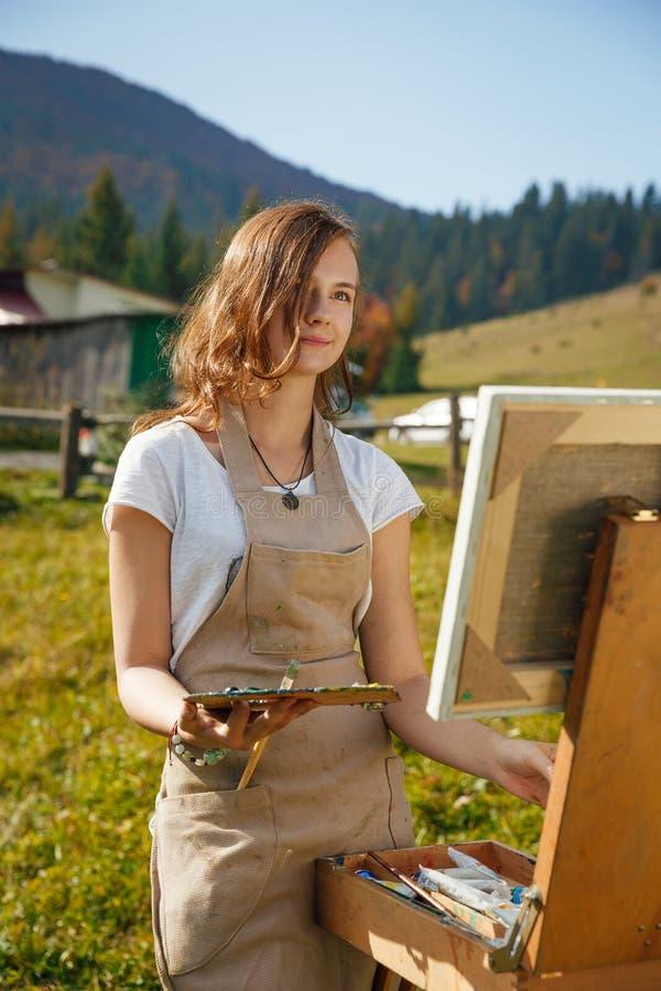 Pintor novo no trabalho nas montanhas foto de stock