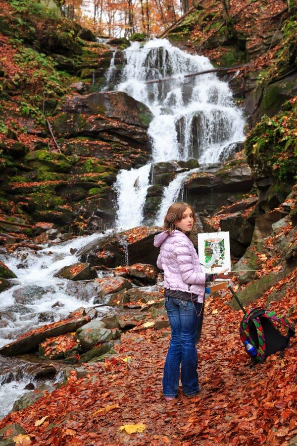 Pintor novo no trabalho perto da cachoeira fotografia de stock