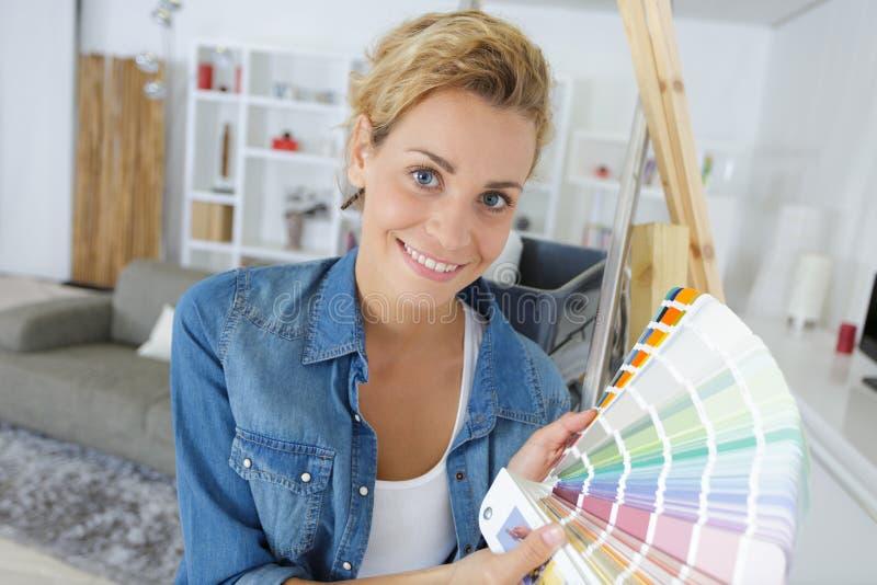 Pintor o decorador de sexo femenino alegre con muestras del color imagenes de archivo