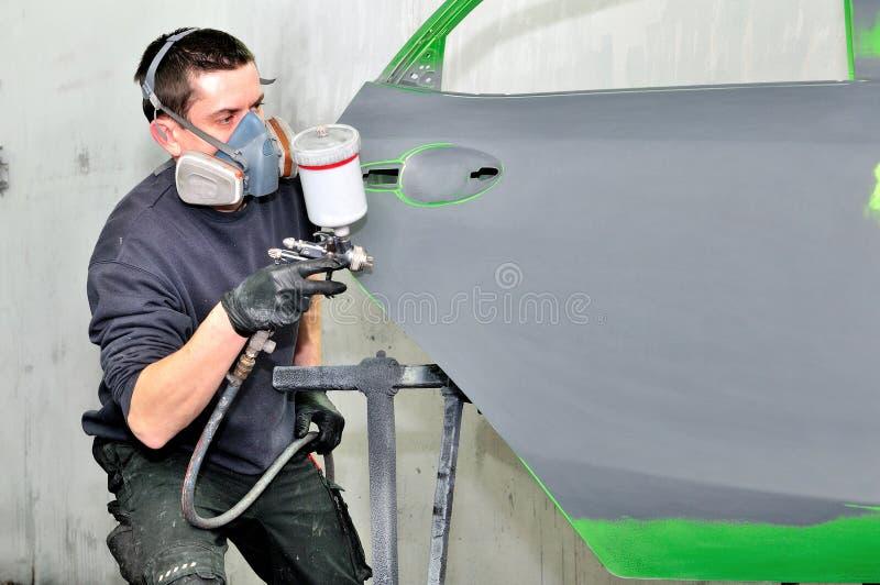 Pintor profissional do carro que trabalha em uma porta imagem de stock royalty free