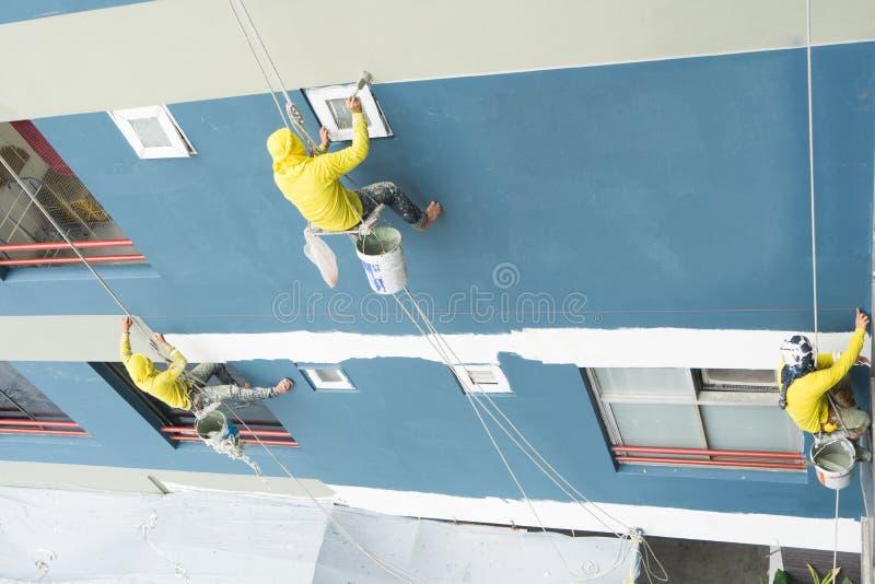 Pintor que cuelga en el rollo, color de pintura en la pared Constructor de la fachada con el cepillo del rodillo, trabajando en l fotos de archivo libres de regalías