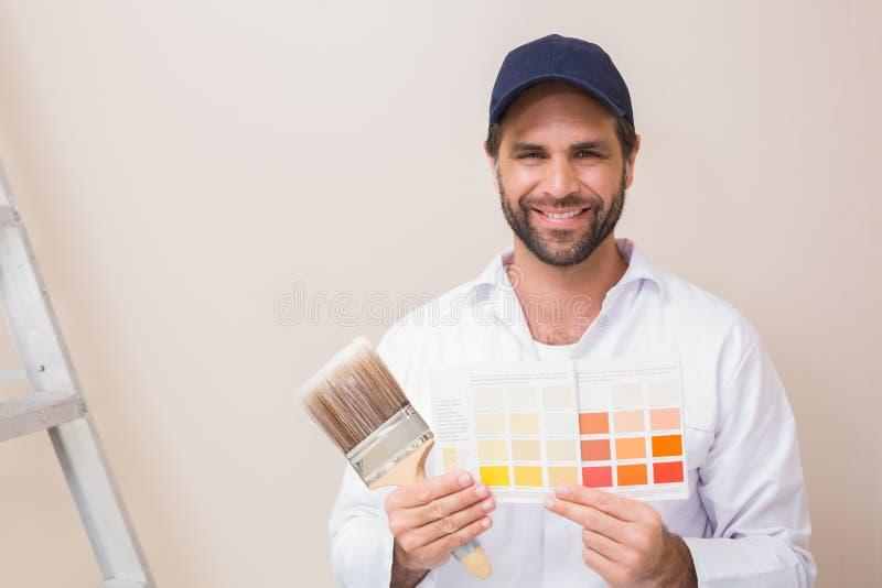 Pintor que guarda uma carta de cor que sorri na câmera fotos de stock royalty free