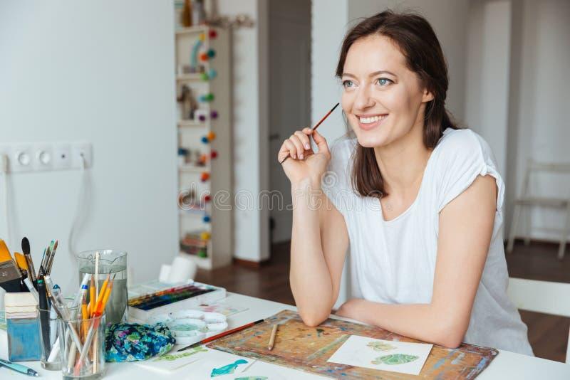 Pintor sonriente de la mujer que sostiene la brocha y que piensa en la tabla fotografía de archivo