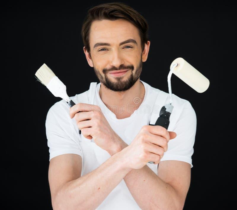 Pintor sonriente que sostiene un rodillo y un cepillo fotografía de archivo