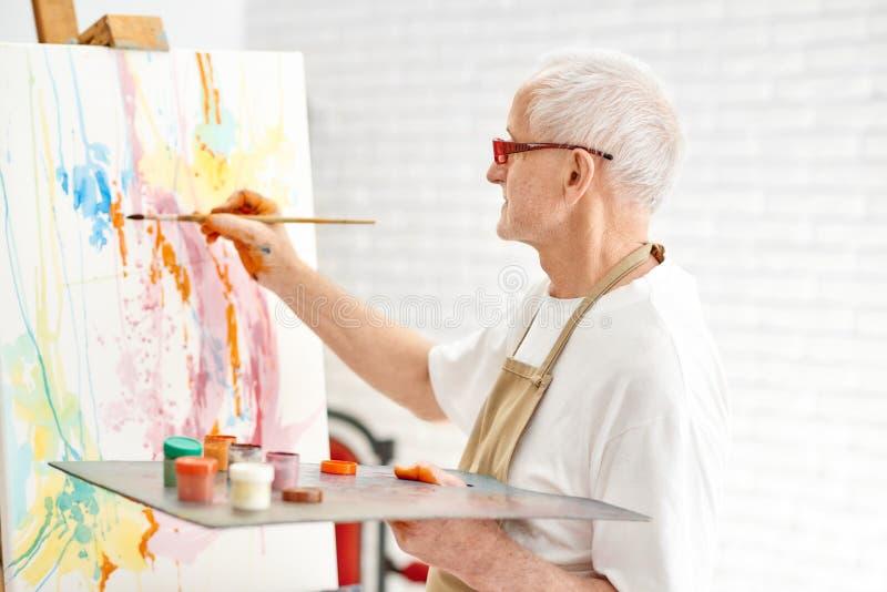 Pintor talentoso mayor mientras que pinta su obra maestra en el estudio foto de archivo