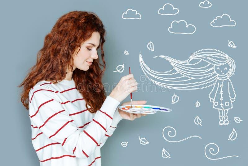 Pintor tranquilo que sostiene una paleta de colores y que parece alegre imágenes de archivo libres de regalías