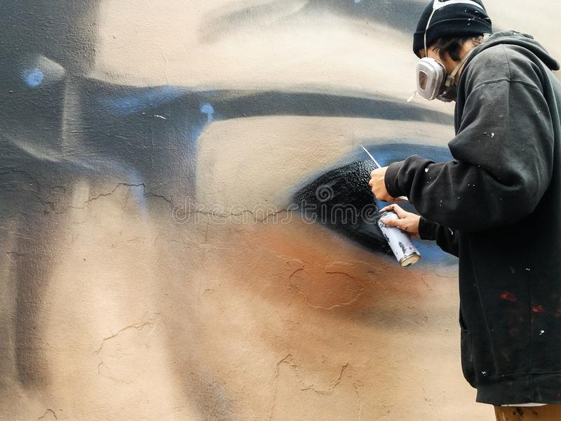 Pintor urbano joven que comienza a dibujar la pintada en la pared en la calle fotos de archivo libres de regalías