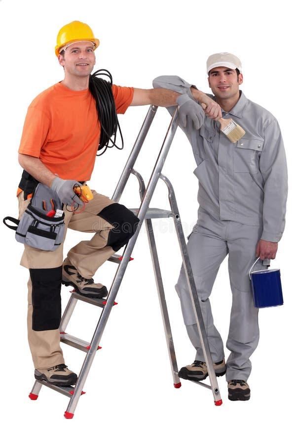 Pintor y electricista por la escalera fotografía de archivo