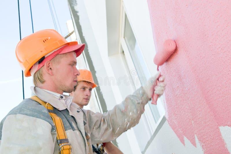 Pintores de la fachada del constructor en el trabajo fotografía de archivo libre de regalías