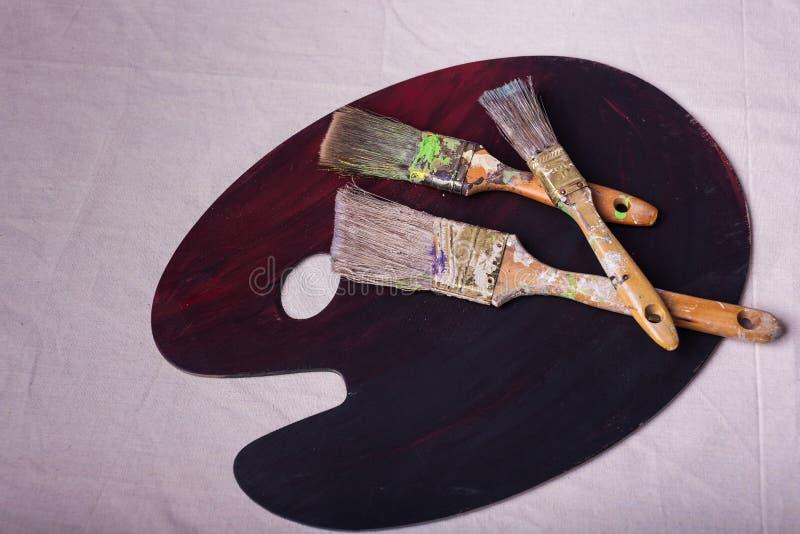 Pintores de madeira que misturam a paleta no contexto da lona dispersado com as escovas de pintura foto de stock