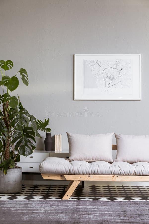 Pintura abstracta de plata en la pared gris sobre futon escandinavo imágenes de archivo libres de regalías
