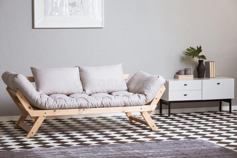 Pintura abstracta de plata en la pared gris sobre futon escandinavo imagenes de archivo