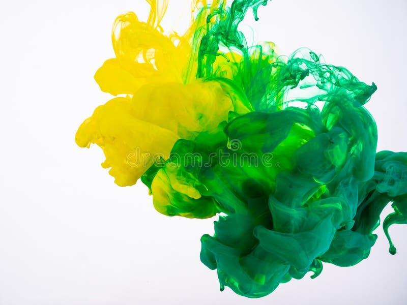 A pintura acrílica amarela e verde faz uma explosão abstrata sob a água Duas cores da tinta que misturam no líquido, isolado sobr fotos de stock royalty free