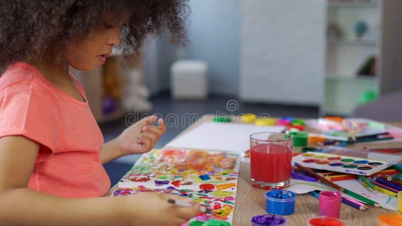 Pintura afro-americana pré-escolar da menina no jardim de infância, lazer criativo da criança fotos de stock