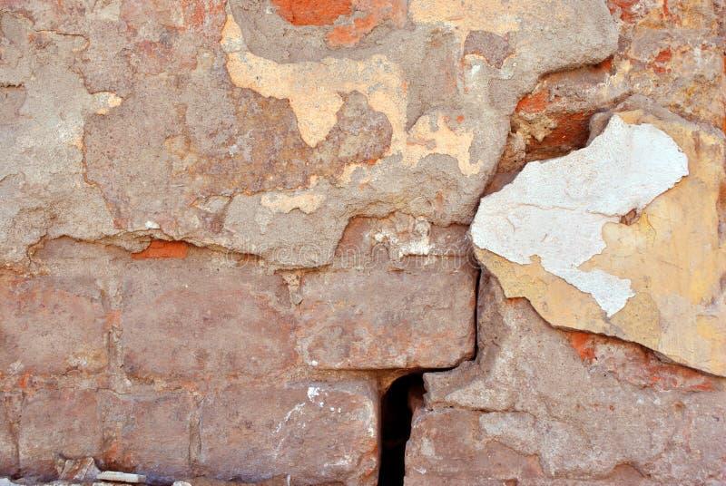 Pintura agrietada, yeso del color en colores pastel amarillo-rojo suave en cierre de la superficie de la pared de ladrillo encima fotografía de archivo libre de regalías