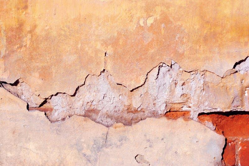 Pintura amarilla agrietada, superficie del yeso en la pared, detalle lamentable horizontal del fondo del grunge imagen de archivo