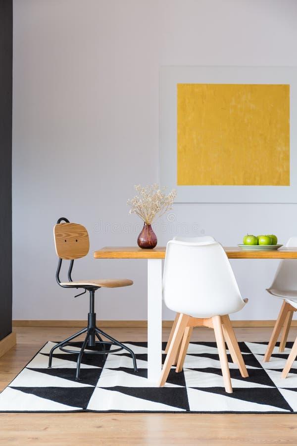 Pintura amarilla que cuelga sobre la tabla foto de archivo