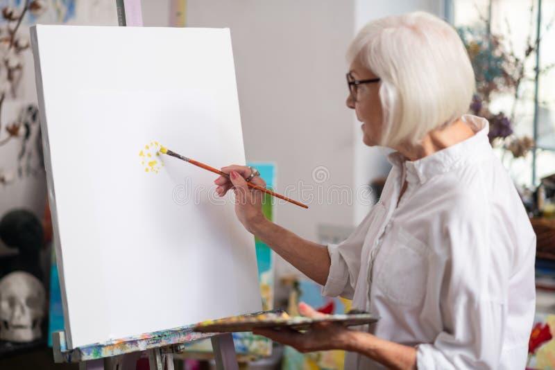 pintura aposentada Louro-de cabelo da mulher com guache amarelo fotografia de stock royalty free