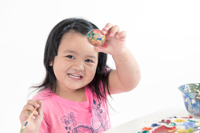 Pintura asiática del niño en el huevo de Pascua fotos de archivo