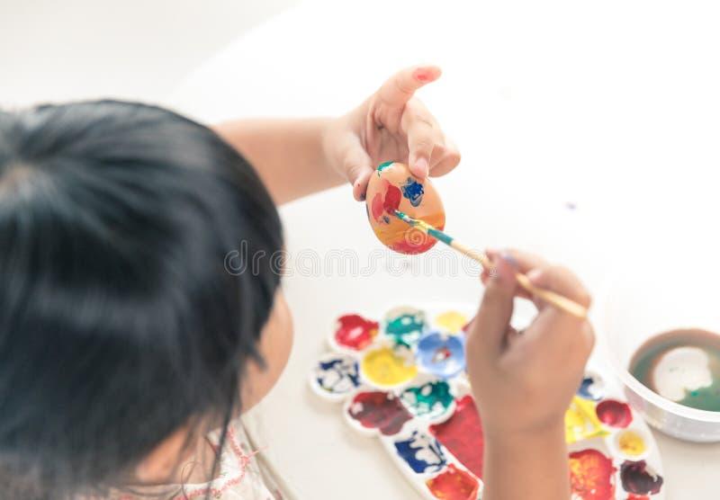 Pintura asiática del niño en el huevo de Pascua foto de archivo libre de regalías