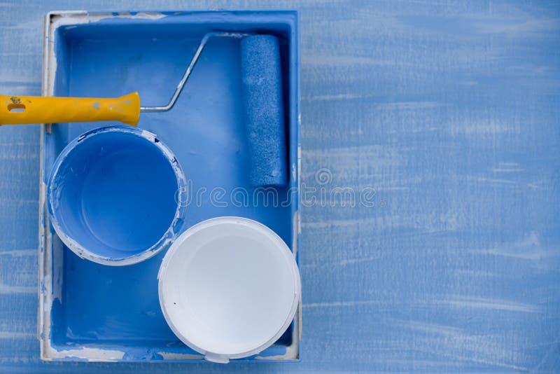 Pintura azul e branca na opini?o superior das latas rolo com um punho amarelo para paredes de pintura foto de stock royalty free