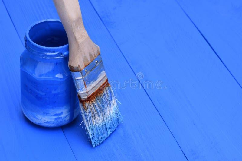 Pintura azul em um frasco com escova fotos de stock