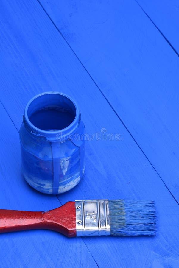 Pintura azul em um frasco com escova foto de stock